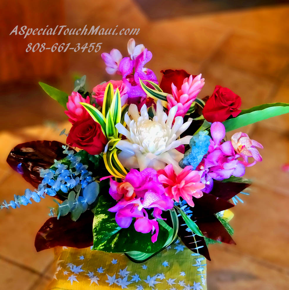 """GINGERS, ROSES, AND ORCHIDS CENTERPIECE $95.00 A lovely combination of Roses, Gingers and Orchids in a Ti Lined Cube Glass Vase 12"""" X 14"""""""